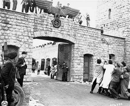Prisoners re-enact the pulling down of the Nazi eagle