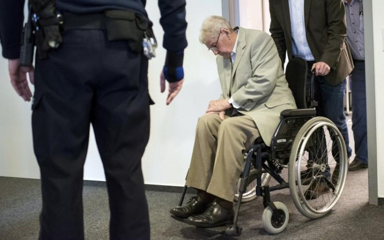 Defendant Reinhold Hanning, a 94-year-old former guard at Auschwitz death camp, is pushed in a wheelchair after a break in his trial in Detmold, Germany, in this file picture taken February 18, 2016. REUTERS/Bernd Thissen/Pool/Files