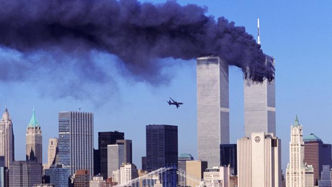 As smoke billows from the north tower, the second hijacked plane bears down on the south tower